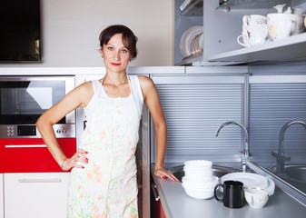 a woman in a clean kitchen with plates