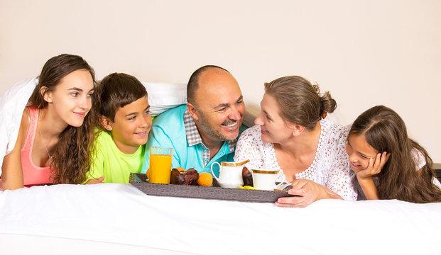 happy smiling joyful family having breakfast in bed