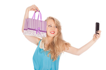 Beautiful girl holding shopping bags taking selfie with phone
