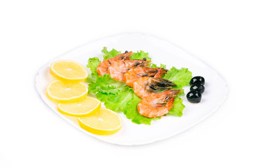 Boiled shrimps with olives and sliced lemon.