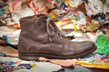 Men's leather boots crumpled sheets of colored paper.