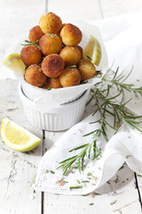 balls of fried potatoes with lemon and rosemary on table