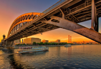 Прогулочный теплоход на Москве реке под мостом на закате