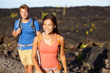 Hiking people - couple walking on lava field