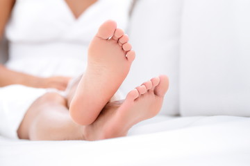 Woman feet closeup - barefoot woman relaxing sofa