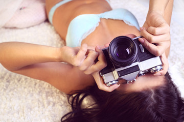 girl in lingerie takes pictures old camera