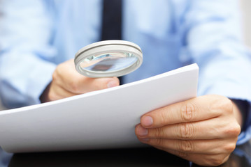 Businessman looking through a magnifying glass to contract