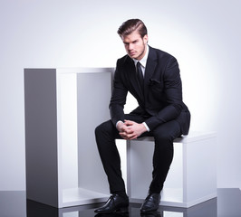 business man sitting on a cube holding his hand together,