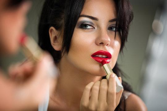 woman applying lipstick looking at mirror