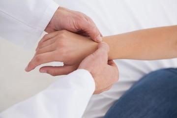 Doctor examining patients wrist