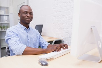 Cheerful creative businessman working on computer