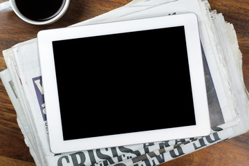 Digital tablet with blank screen on newspaper