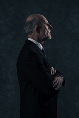 Senior businessman with gray beard wearing dark suit. Against gr