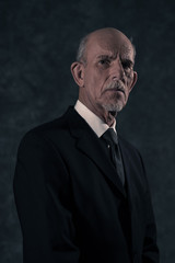 Serious senior businessman with gray beard wearing dark suit and