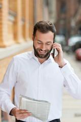 mann mit zeitung telefoniert mit handy
