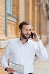 mann mit tageszeitung telefoniert