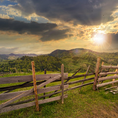 fence on hillside meadow in mountain at sunset