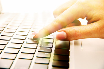 Female hand on laptop, close up