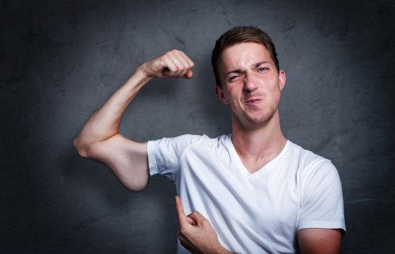 Junger mann zeigt auf seinen verkümmerten Arm