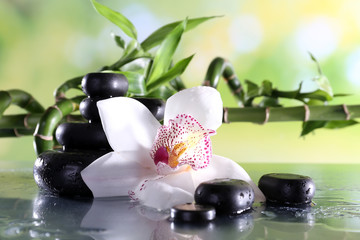 Spa stones and white orchid on table on natural background