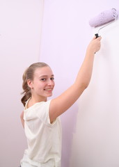 Girl paints wall in lilac color with roller