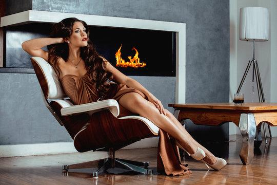 beauty yong brunette woman sitting near fireplace at home