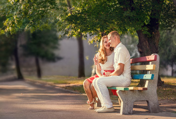 Loving couple sitting on banch in park