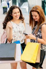 Shopping girls texting on phone