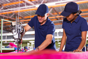 senior textile worker teaching new employee about cutting fabric