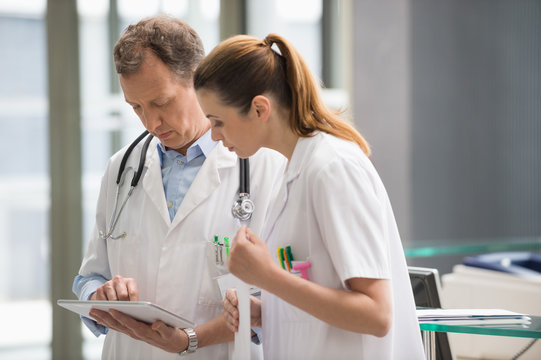 Two doctors analyzing medical report on digital tablet in hospital