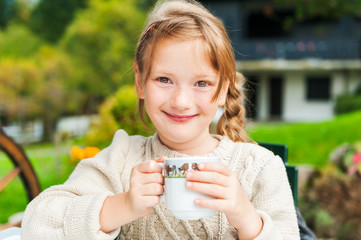 Cute little girl drinking hot chocolate outdoors