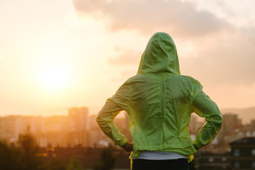 Athlete looking sunset over city skyline after exercising