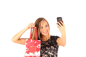 Beautiful girl holding shopping bags and taking selfie with