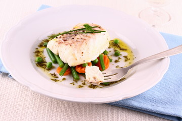 Cod fillet on fork with green beans, peas, parsley, olive oil