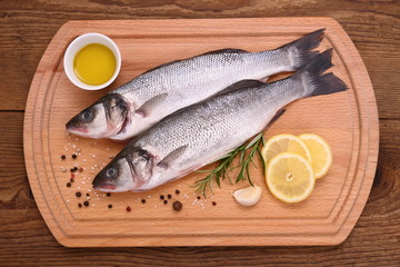 Two fresh moronidae fish on cutting board with ingredients