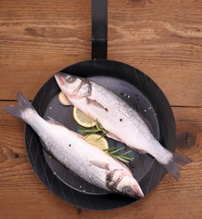 Two fresh sea bass fish on frying pan with ingredients