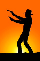 Wall Mural - cowboy silhouette with two pistols sunset