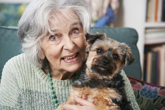 Senior Woman Holding Pet Dog Indoors