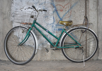 green old bicycle and the wall