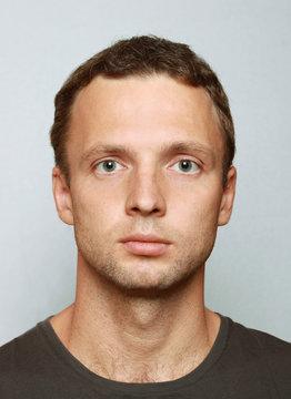 Young Caucasian man closeup portrait. Headshot on gray