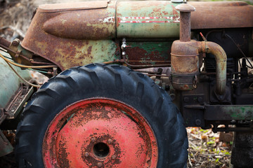 Fragment of old rusted green tractor with red wheel