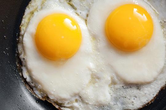 Macro photo of two scrambled eggs in black frying pan