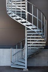 Foto op Plexiglas Trappen Modern metal spiral staircase above dark gray wall