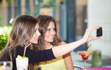 Two female young friends taking a selfie portrait