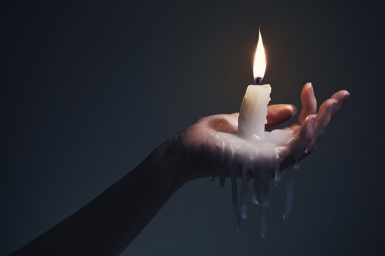 Holding a candle on a dark background.