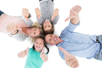 Smiling family lying on the floor in a circle showing thumbs up