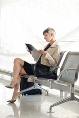 Businesswoman reading newspaper at Charles de Gaulle airport, Pa