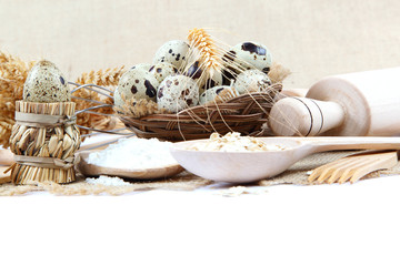 Quail eggs, flour and cooking utensils on canvas.