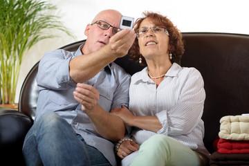 a senior couple looks at a photograph slide