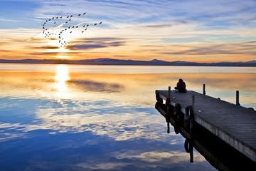 Photo sur Aluminium Jetee gente en el embarcadero mirando el amanecer